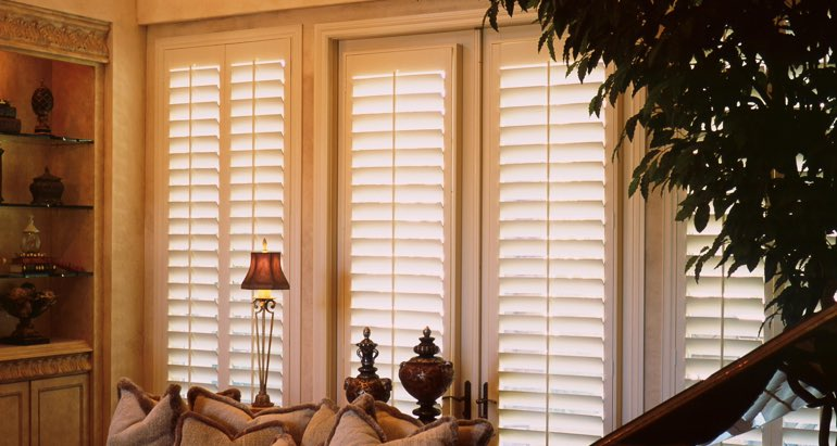 Plantation shutters on french door and window in Dallas lounge