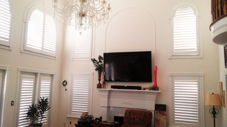 Dallas great room with mounted TV and arched windows.