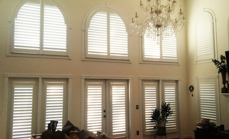 Entertainment room in open concept Dallas home with plantation shutters on high ceiling windows.