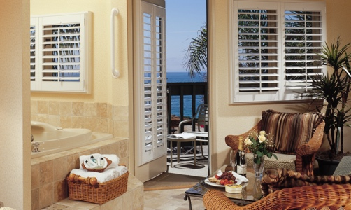 Plantation shutters on casement windows in a tropical condo.