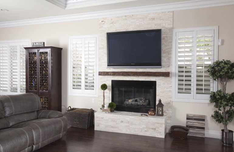 White plantation shutters in a Dallas living room with plank hardwood floors.