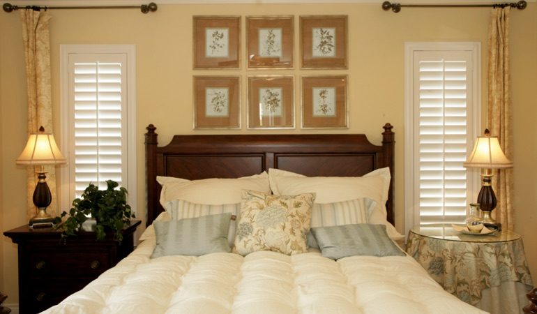 Beige bedroom with white plantation shutters covering windows in Dallas