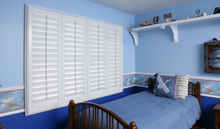 Blue kids bedroom with white plantation shutters in Dallas